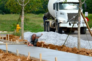 A Craftsman from John Russell's crew carefully sculps the new sidewalks along Dewitt Drive