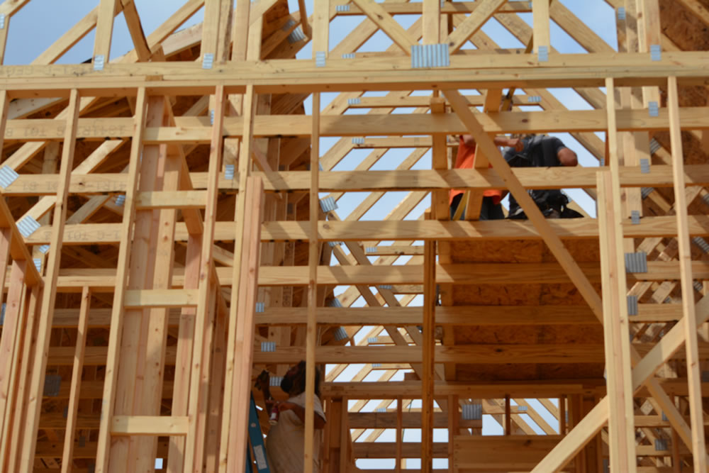 Workers climb through a maze of intricate woodwork at one of LENDONs quality Westmark Homes